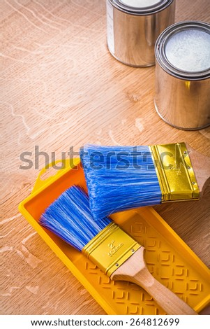 paint brushes on tray and metalic paint cans construction concept  - stock photo