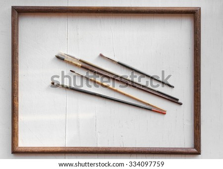 Paint brushes on white wooden background in wooden frame.  - stock photo