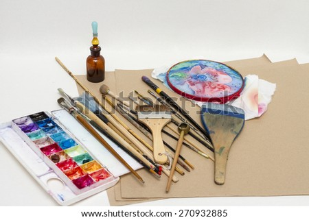 Paint brushes, paint and drawing tools on the table of the artist. - stock photo