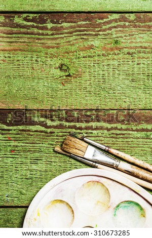 Paint brushes set and a palette on a green wooden background - stock photo