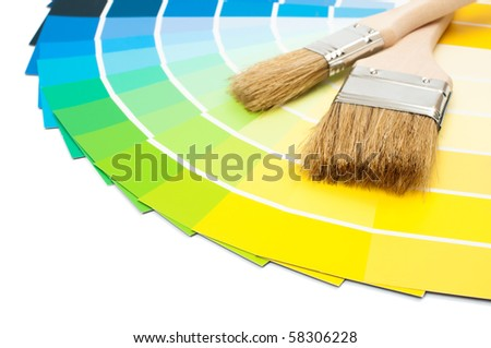 Paint brushes with colour swatch cards on white background - stock photo