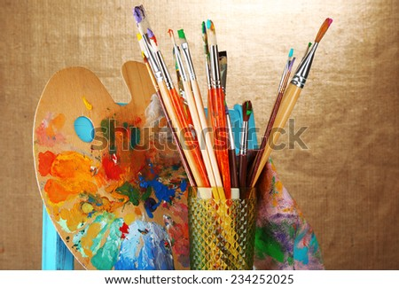 Paint brushes with paints and palette on beige background - stock photo