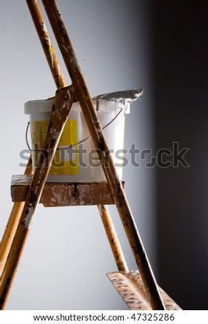 Paint bucket and paintbrush at stepladder over gray wall