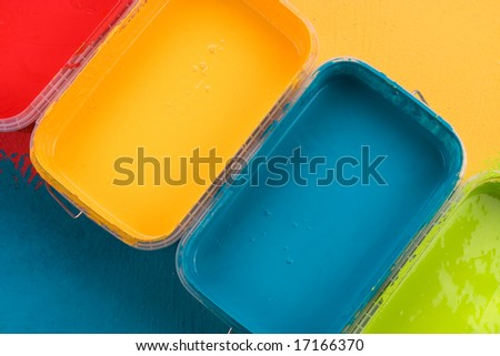Paint cans with yellow, blue, red and green paint - stock photo