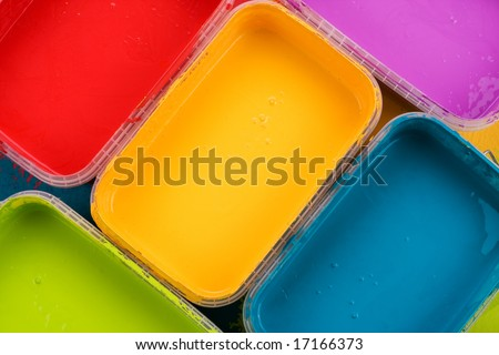 Paint cans with yellow, blue, red, magenta and green paint - stock photo