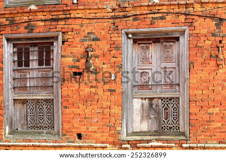 Paint-faded old carved wooden windows on the red brick facade of a traditional newari style house in the old city area. Dhulikhel-Kavrepalanchok distr.-Bagmati zone-Nepal. - stock photo