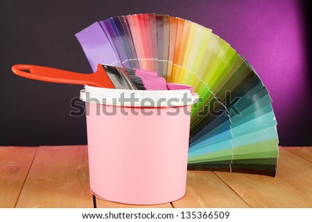 Paint pot, paintbrush and coloured swatches on wooden table on dark purple background - stock photo