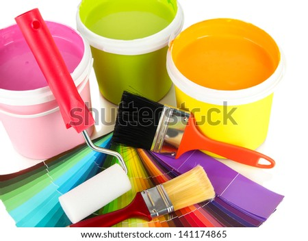 Paint pots, paintbrushes and coloured swatches close up - stock photo