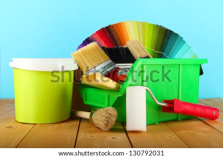 Paint pots, paintbrushes and coloured swatches on wooden table on blue background - stock photo