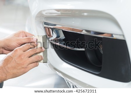 Paint protection film series : Installing paint protection film on white car - stock photo