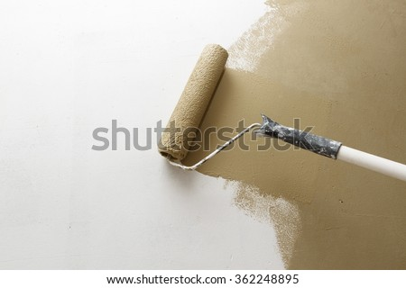 Paint roller applying brown paint on white wall, home improvements, horizontal view with copy space - stock photo