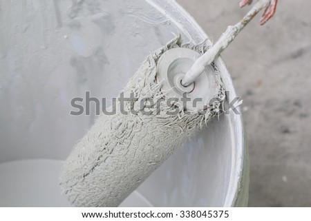 Paint roller is placed on the edge of the paint bucket.