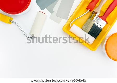 paint rollers in tray, brushes, and paint cans with color sample