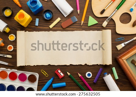 paint supplies and brush on wooden background - stock photo