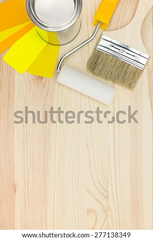 paint tin can, brush with roller and color palette on wooden background - stock photo