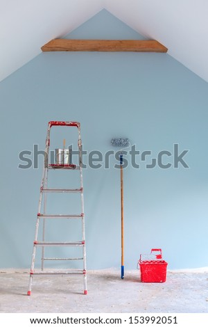 Paint tools with ladder against a newly painted light blue  wall - stock photo