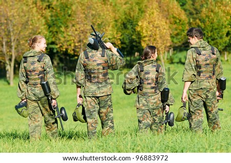paintball extreme sport players team in protective camouflage uniform and mask with markers gun in summer field