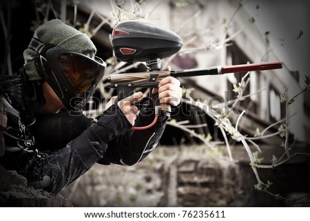 Paintball player aiming with marker in grunge background - stock photo