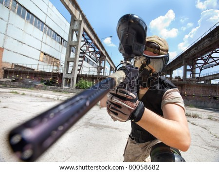 Paintball player over industrial background, close up shot - stock photo