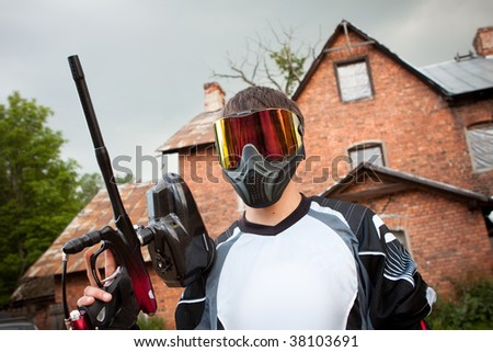 paintball shooter and house as the background - stock photo