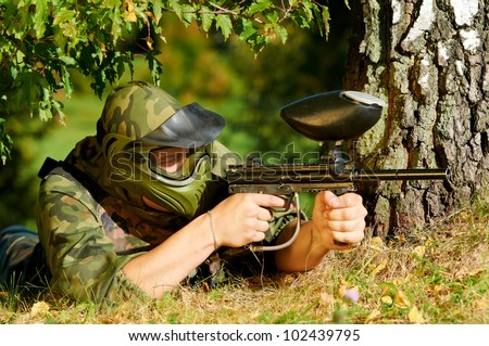 paintball sport player in protective uniform and mask aiming and shooting with marker paintballing gun outdoors - stock photo
