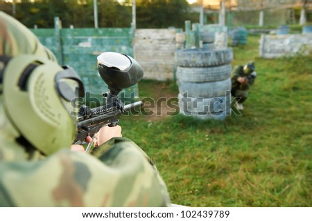 paintball sport player in protective uniform and mask aiming and shooting with paintballing marker gun outdoors
