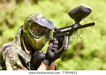 paintball sport player in protective uniform and mask aiming gun before shooting in summer - stock photo