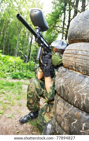 paintball sport player in protective uniform and mask making gunfire to enemy from shelter outdoors - stock photo