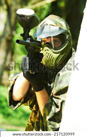 paintball sport player man in protective camouflage uniform and mask with marker gun outdoors - stock photo