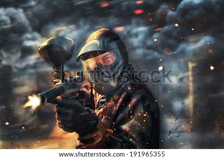 paintball sport player wearing protective mask shooting
