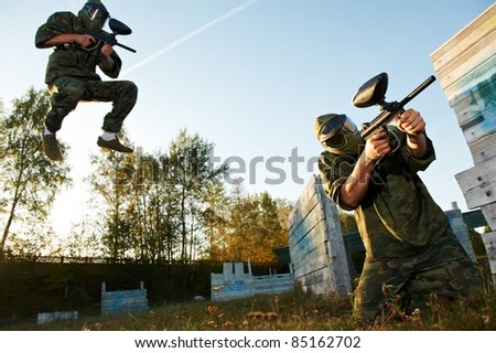 paintball sport players during tactical training game attack in forest with protective uniform and masks