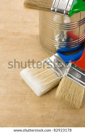 paintbrush and can on wood background texture