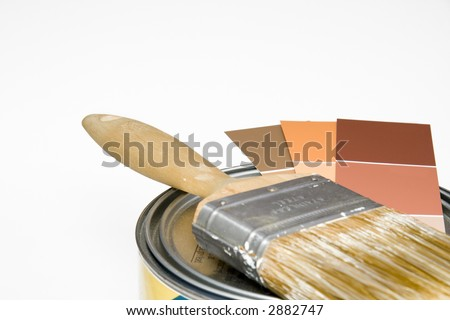Paintbrush and color swatches on top of can of paint - stock photo