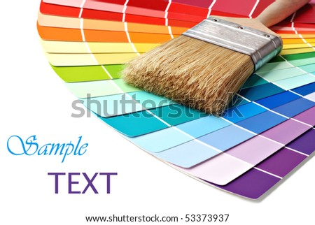 Paintbrush and colorful paint samples on white background with copy space.