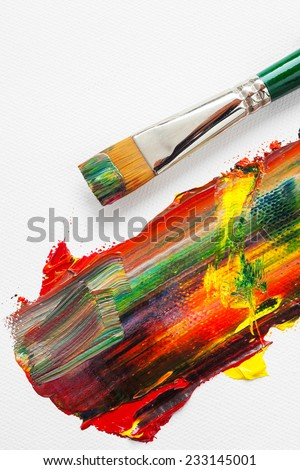 Paintbrush and mixed rainbow oil paints on white artist canvas - stock photo
