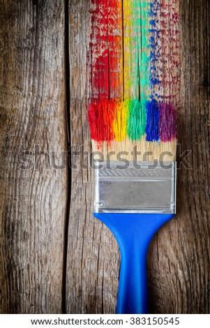 Paintbrush and multicolor rainbow brush strokes on wooden plank - stock photo
