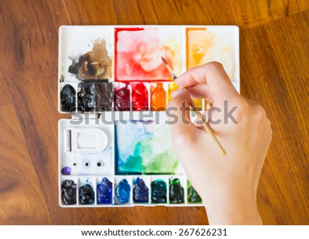 Paintbrush and paint palette with artist's hand holding brush painting colorful mixed watercolor - stock photo