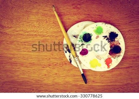 paintbrush and watercolor pallete on wooden background ,vintage tone - stock photo