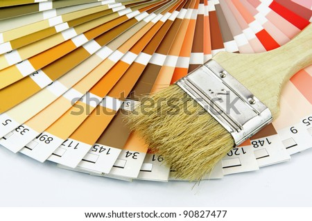 Paintbrush and wheel of colorful paint swatches. - stock photo