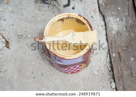paintbrush on yellow paint can. - stock photo