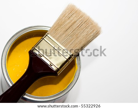 paintbrush on yellow paint can - stock photo