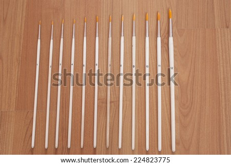 Paintbrush set, different size round brushes with easy-to-clean polyester bristles, on brown wooden background - stock photo