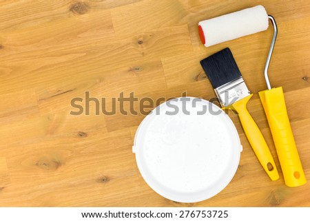 paintbrush with roller and paint can on wooden background - stock photo