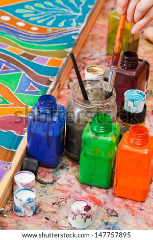 paintbrushes and bottles with color pigments for cold batik