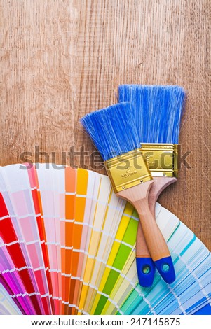 paintbrushes and color  palette on brown wooden board with copyspace - stock photo