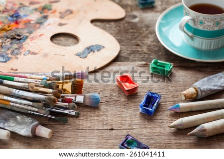 Paintbrushes, artist palette, pencils, coffee cup, watercolor and oil paints on desk in painter studio. - stock photo