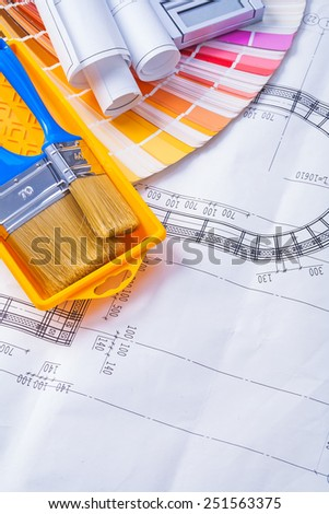 paintbrushes in paint can and rolled blueprints on color pallete  - stock photo