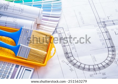 paintbrushes in paint can and rolled blueprints on color pallete horizontal version  - stock photo