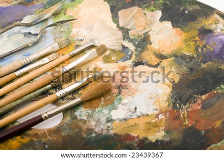 Paintbrushes laying on an old used palette with colors all over - stock photo
