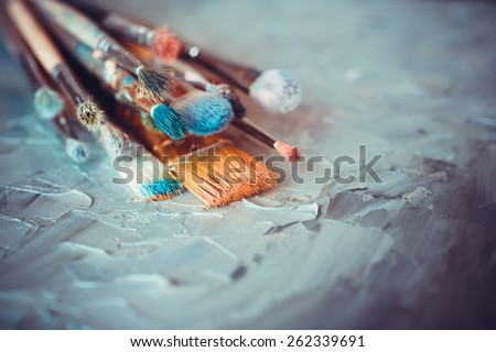 Paintbrushes on artist canvas covered  with oil paints - stock photo